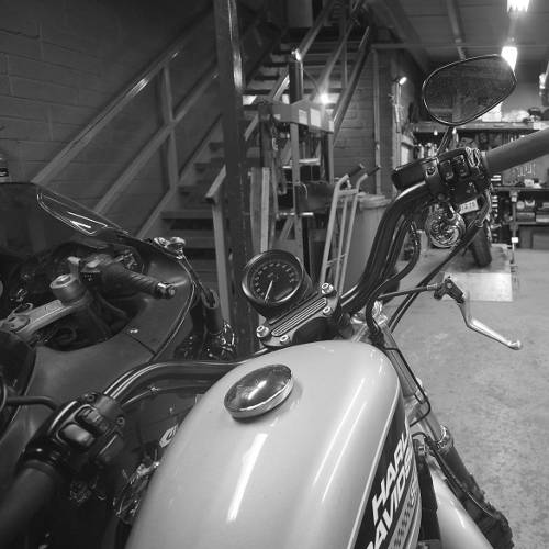 A black and white photo of 2 bikes in the garage